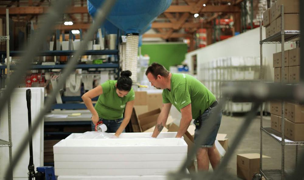 Two fulfillment warehouse workers carefully pack an order.