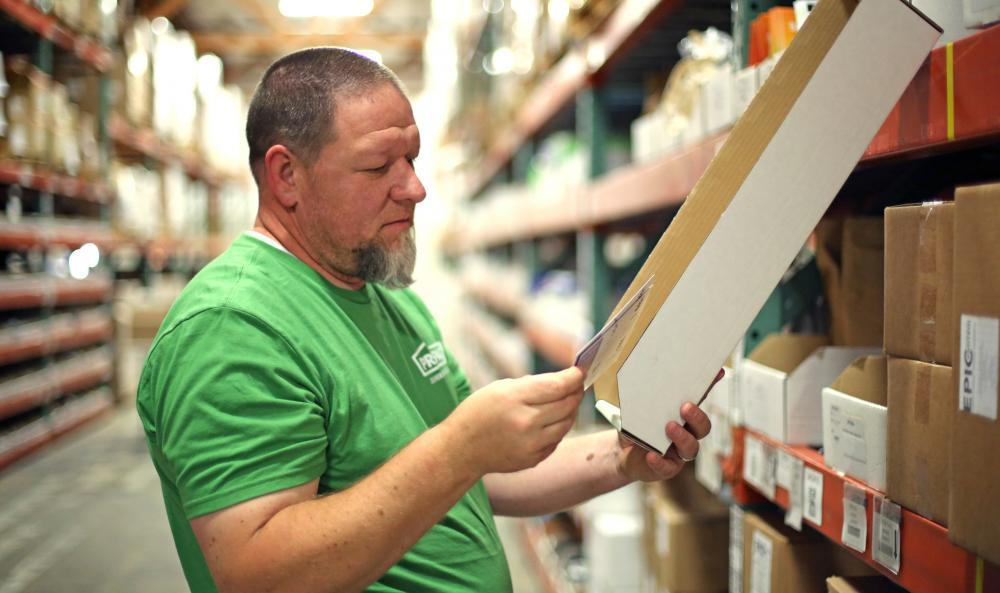 Warehouse worker careful inspects an order